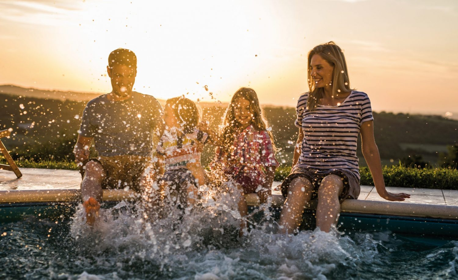Playful Family Having Fun While Splashing Water From The Pool At Sunset.